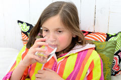 A sick girl drinking a glass of water royalty free stock image