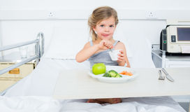 Sick girl eating healthy food in hospital Royalty Free Stock Photos