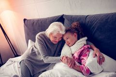 Sick girl feeling grateful while caring granny supporting her. Girl feeling grateful. Sick girl wearing beige scarf feeling grateful while caring granny royalty free stock photo