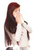 Sick girl with flu blowing her nose Stock Image