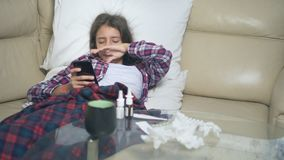 Sick girl holding a smartphone. cold teen girl covers with winter flu blanket resting at home. stock video footage