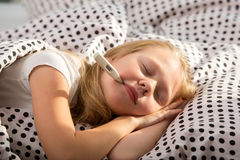 Sick girl holding thermometer laying in bed Royalty Free Stock Images