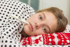 Sick girl holding thermometer laying in bed Stock Photos