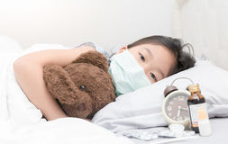 Sick girl with hygienic mask laying on bed stock photos