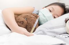 Sick girl laying on bed and holding thermometer in hand royalty free stock images