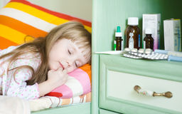 Sick girl lying on a bed Stock Photos