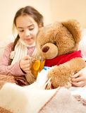 Sick girl lying in bed and giving tea to teddy bear Royalty Free Stock Photography