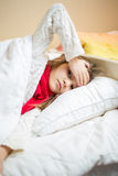 Sick girl lying in bed and holding hand on head Royalty Free Stock Photos