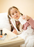 Sick girl lying in bed and holding paper tissue Stock Image