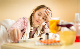 Sick girl lying in bed and taking thermometer from bedside table Stock Image