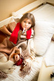 Sick girl lying in bed with teddy bear and measuring temperature Stock Images