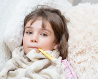 Sick girl lying in bed with a thermometer in mouth.  Royalty Free Stock Image