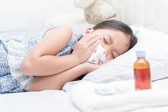 Sick girl lying in bed and use mask to stop sneeze Stock Image