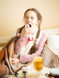 Sick girl lying in bed and using throat spray. Little sick girl lying in bed and using throat spray Stock Photos