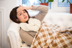 Sick girl lying on the couch with a headache Royalty Free Stock Image