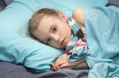 Sick girl lying in her bed. Sick girl with the scarf  lying in her bed Royalty Free Stock Photo