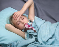 Sick girl lying in her bed Royalty Free Stock Photos