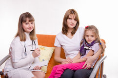 Sick girl measures the temperature of sitting on lap mother and doctor writes a complaint Royalty Free Stock Photography