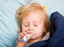 A sick girl is measuring the temperature Stock Photo