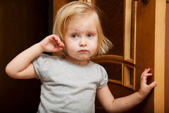 A sick girl is near the door royalty free stock photo