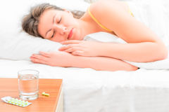 Sick girl. Pills and a glass of water for the sick girl Stock Photography