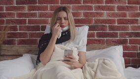 A sick girl with a scarf around her neck is lying in bed, holding her phone in her hand, wiping the sweat from her