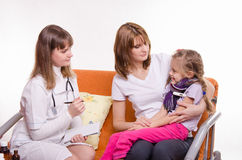 Sick girl sitting on lap of mother and pediatrician inspection Royalty Free Stock Images