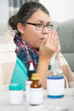 Sick girl  in sofa with medications on a bedside table. Stock Images