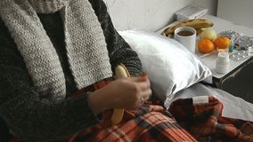 Sick girl in the sweater lies in bed and eats a banana. At home stock video