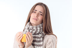 Sick girl in  sweater and scarf holding  hot cup of isolated on white background Royalty Free Stock Photo