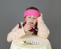 Sick girl takes pills Stock Image