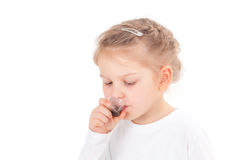 Sick girl taking cough syrup. Isolated on white background Royalty Free Stock Photography