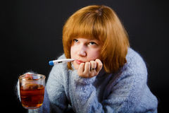 Sick girl with tea and a thermometer Stock Photos