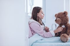 Sick girl and teddy bear Stock Image
