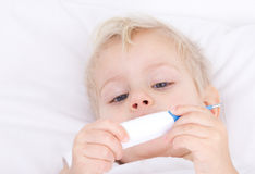 Sick girl with thermometer. Little sick girl in bed wiith thermometer in hands Royalty Free Stock Photo