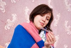 Sick girl thermometer in a bathrobe Royalty Free Stock Image