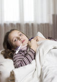 Sick girl. A sick girl,with a thermometer in her mouth. She has stripped pullover and colored scarf Stock Photos