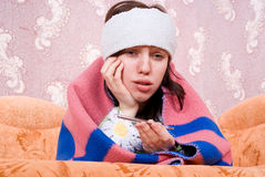 Sick girl with a thermometer at home Royalty Free Stock Image