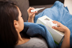 Sick girl with a thermometer Stock Images