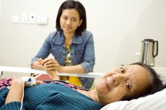 Sick grandma visit by granddaughter. Sick asian grandmother seems happy visited by her granddaughter. having bed resting in inpatient treatment at the hospital Royalty Free Stock Image