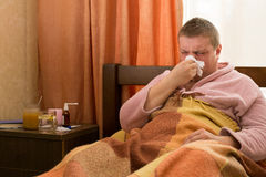 Sick guy in a pink bathrobe, lying in the bed and blowing Royalty Free Stock Images