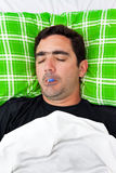 Sick hispanic man laying in bed with a thermometer Stock Images