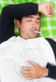 Sick hispanic man laying in bed with a thermometer. Portrait of a sick hispanic man laying in bed with a thermometer in his mouth and his eyes closed Stock Photos