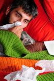 Sick at home with the cat. A sick man at home, laying down with his cat and tissue paper Stock Photography