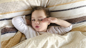 Sick or ill child in bed. Sleepy sick or ill child lying in a bed, waking up in the morning Stock Photo
