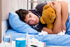 The sick ill man in the bed taking medicines and drugs Royalty Free Stock Image