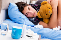 The sick ill man in the bed taking medicines and drugs. Sick ill man in the bed taking medicines and drugs Royalty Free Stock Images