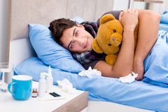 The sick ill man in the bed taking medicines and drugs. Sick ill man in the bed taking medicines and drugs Stock Images