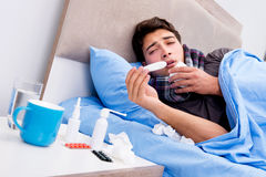 The sick ill man in the bed taking medicines and drugs Stock Image