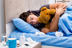 The sick ill man in the bed taking medicines and drugs Stock Photos